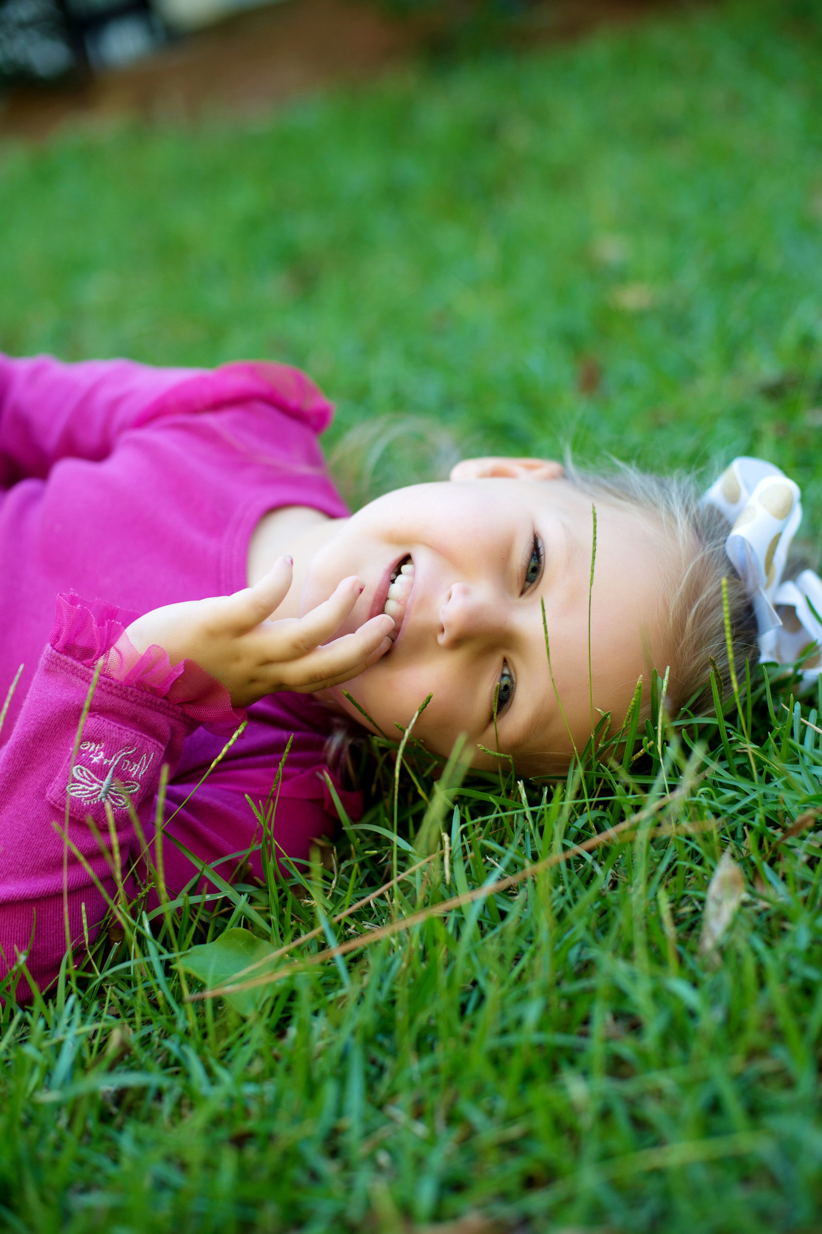 a girl lays in the grass and laughs