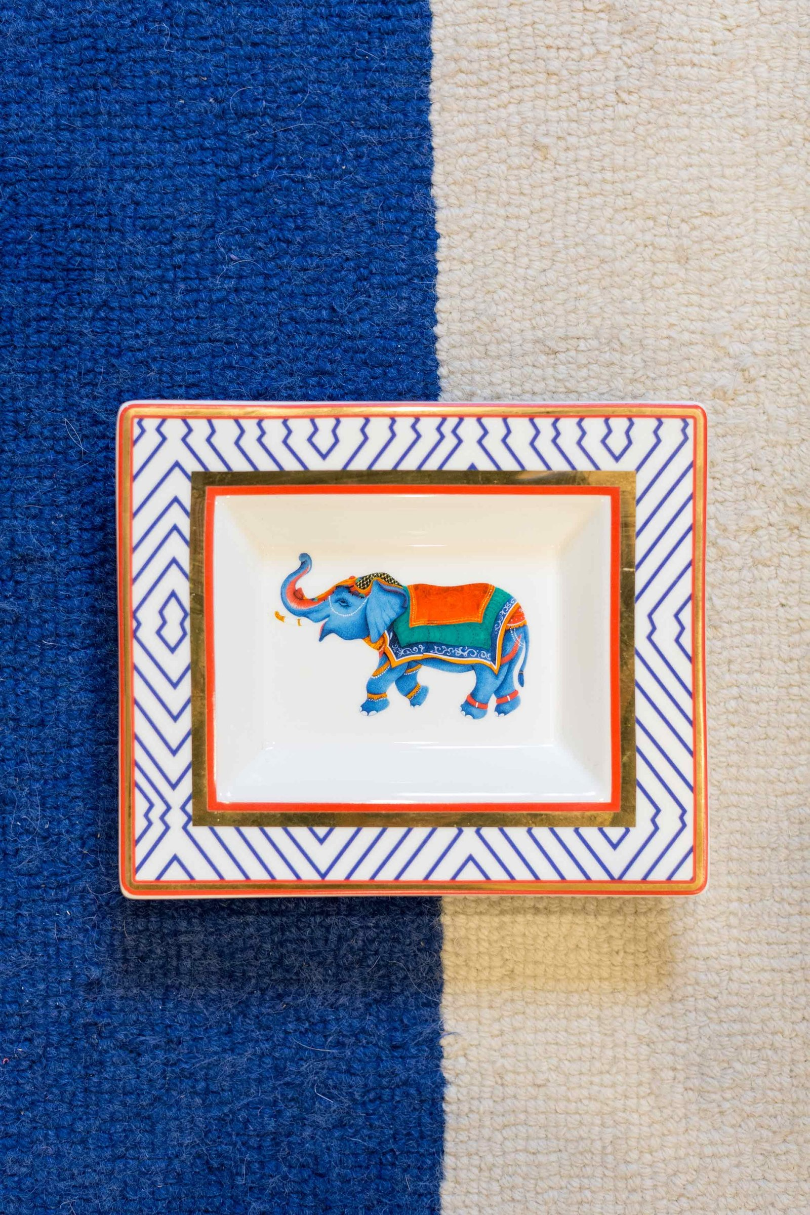 A ceramic dish with an elephant on top of a blue and white rug.