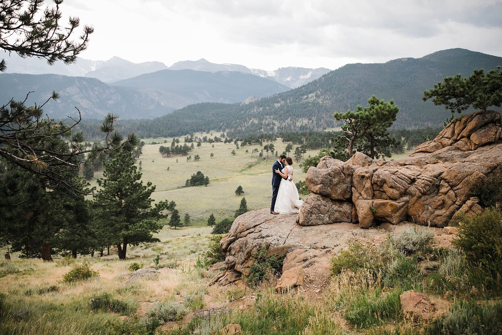 bride and groom hold each other at rocky mountain national park