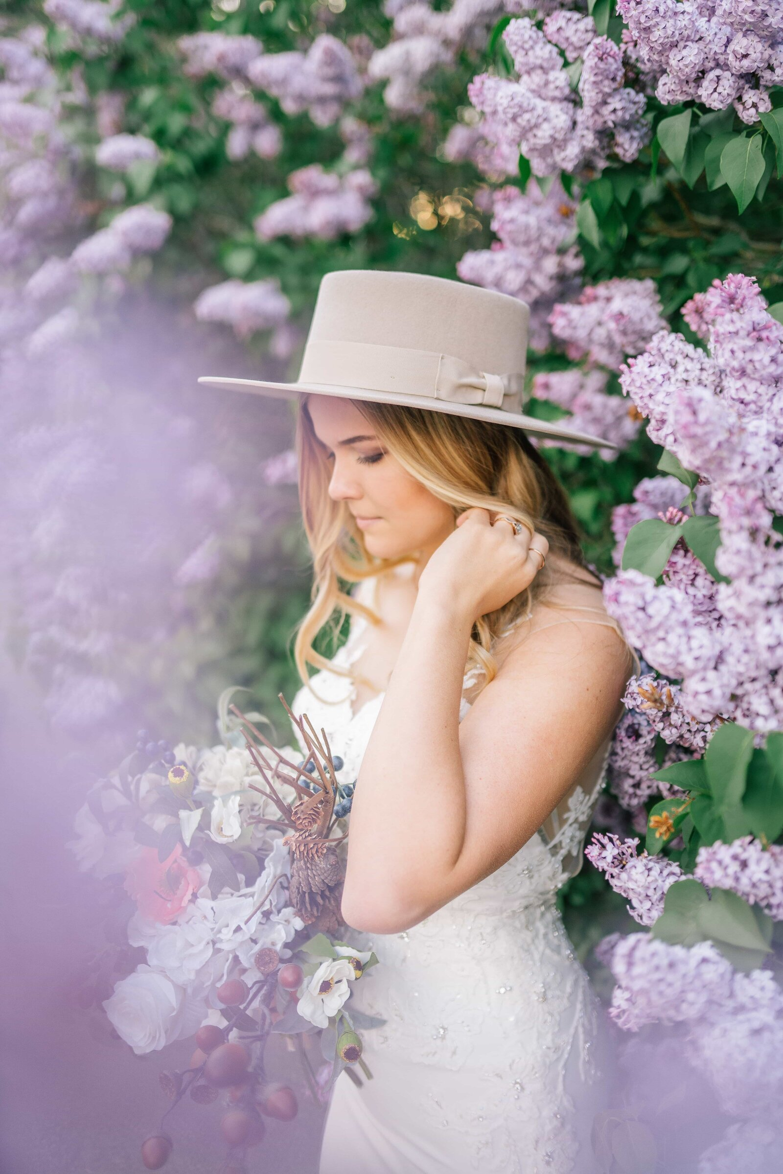 bride with hat next to purple blossoms in Knoxville Tennessee