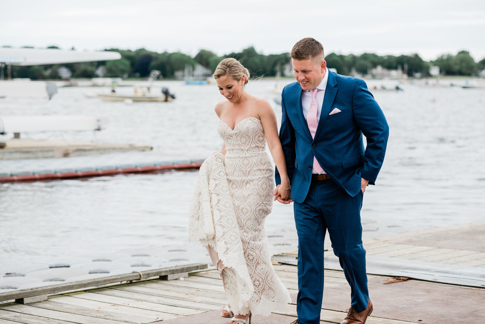 A couple taking their portraits on the dock at a Duxbury Bay Maritime School wedding