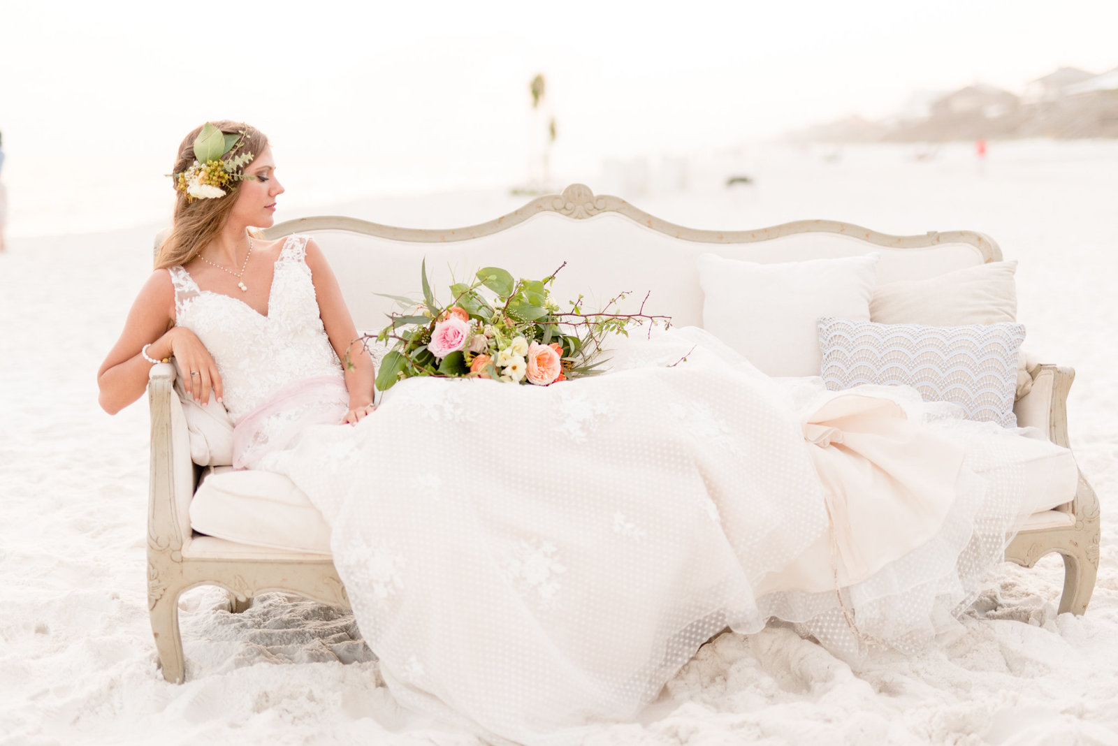 Bride sits on couch during bridal, beach portraits.