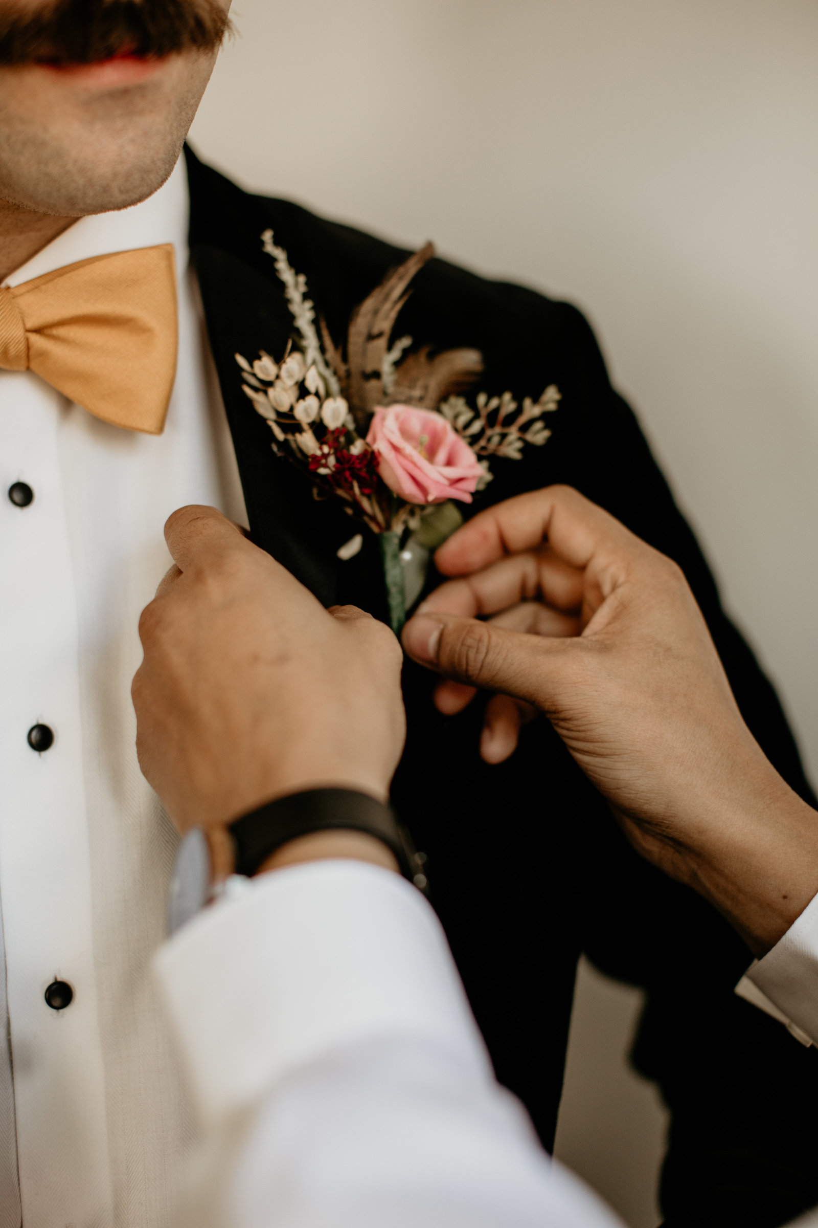 Grooms boutonnière is fasten to his suit jacket.