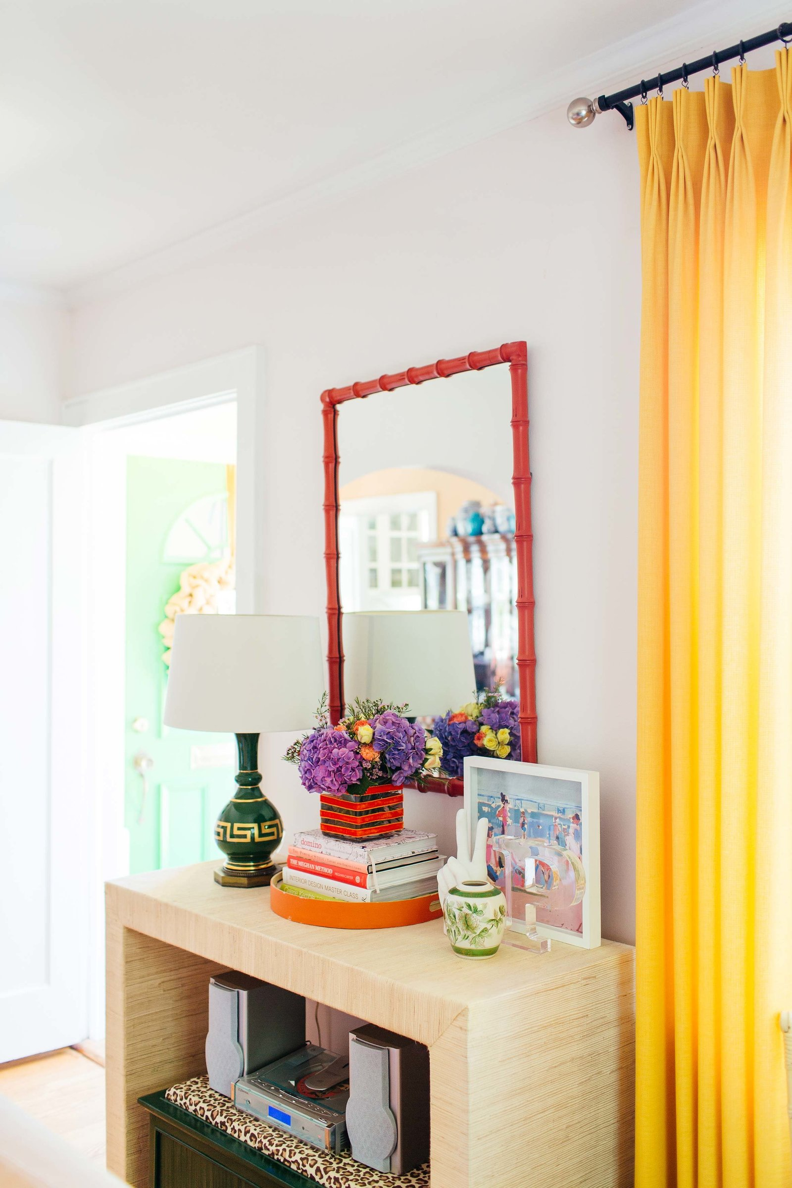 An entryway table with a lamp, mirror, and accessories.