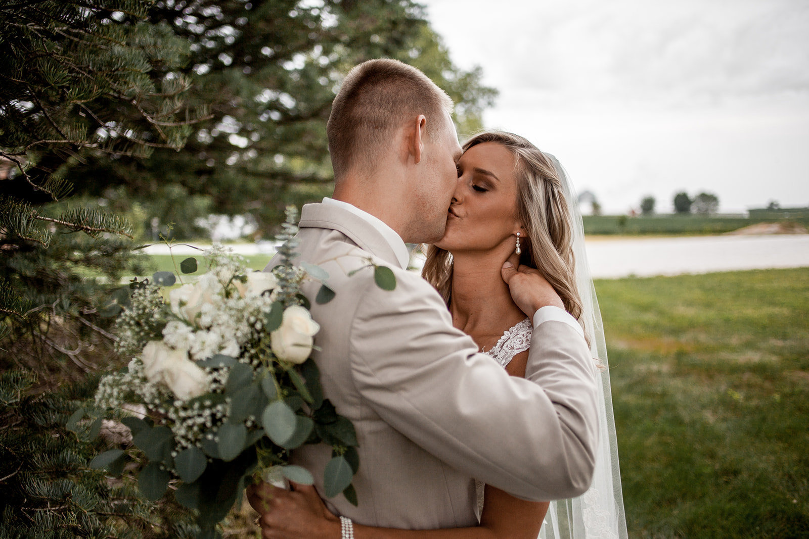 Des Moines Iowa wedding couple kissing in a field.