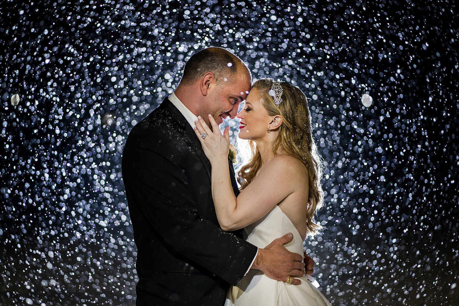 bride and groom stand with foreheads touching surrounded by falling snow at their January wedding
