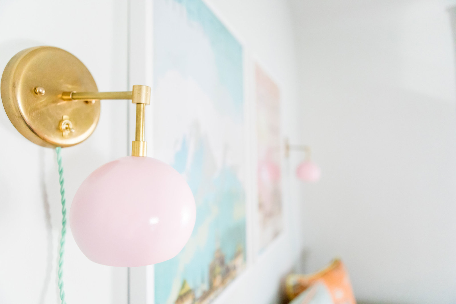 Gold and pink globe sconces in a nursery.