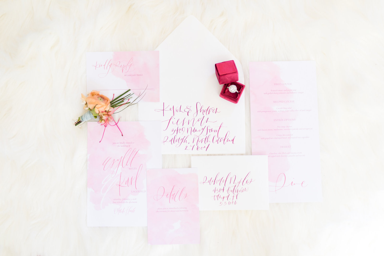 Pink Watercolor Invitation Suite sits on rug.