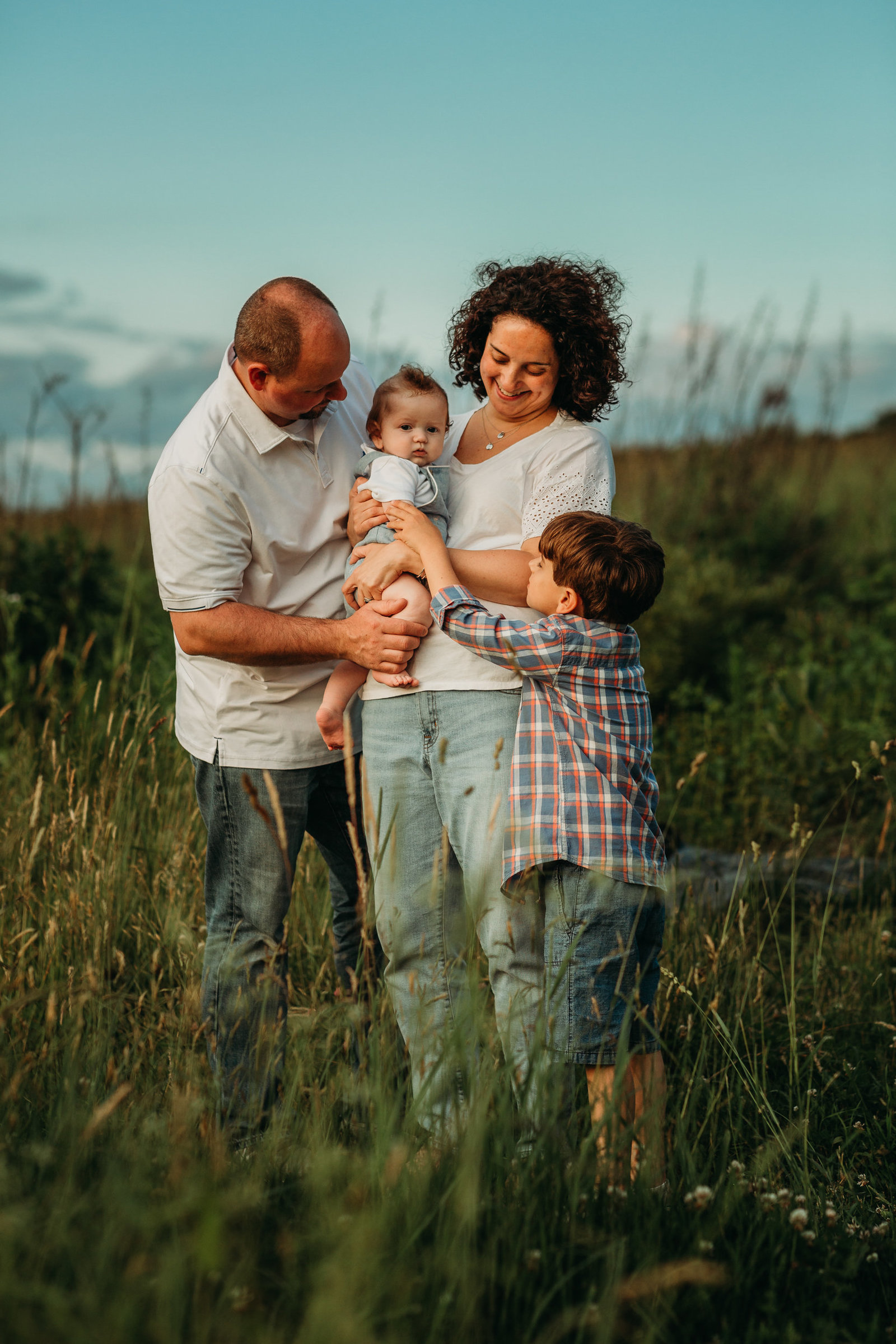 family look lovingly at baby brother in field during outdoor family photos in framingham ma