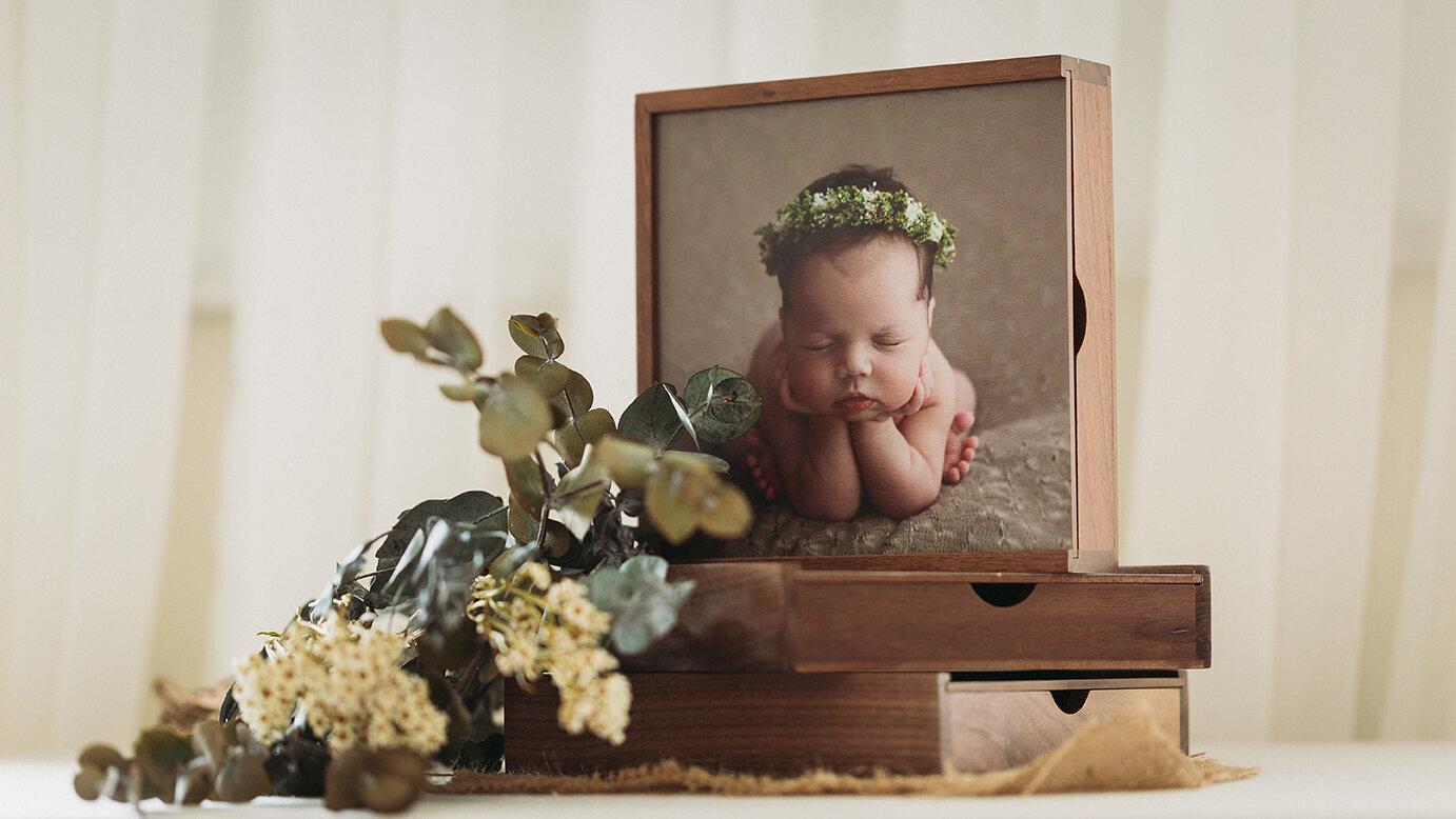 Photo of professional wooden box set featuring newborn baby posed in-studio