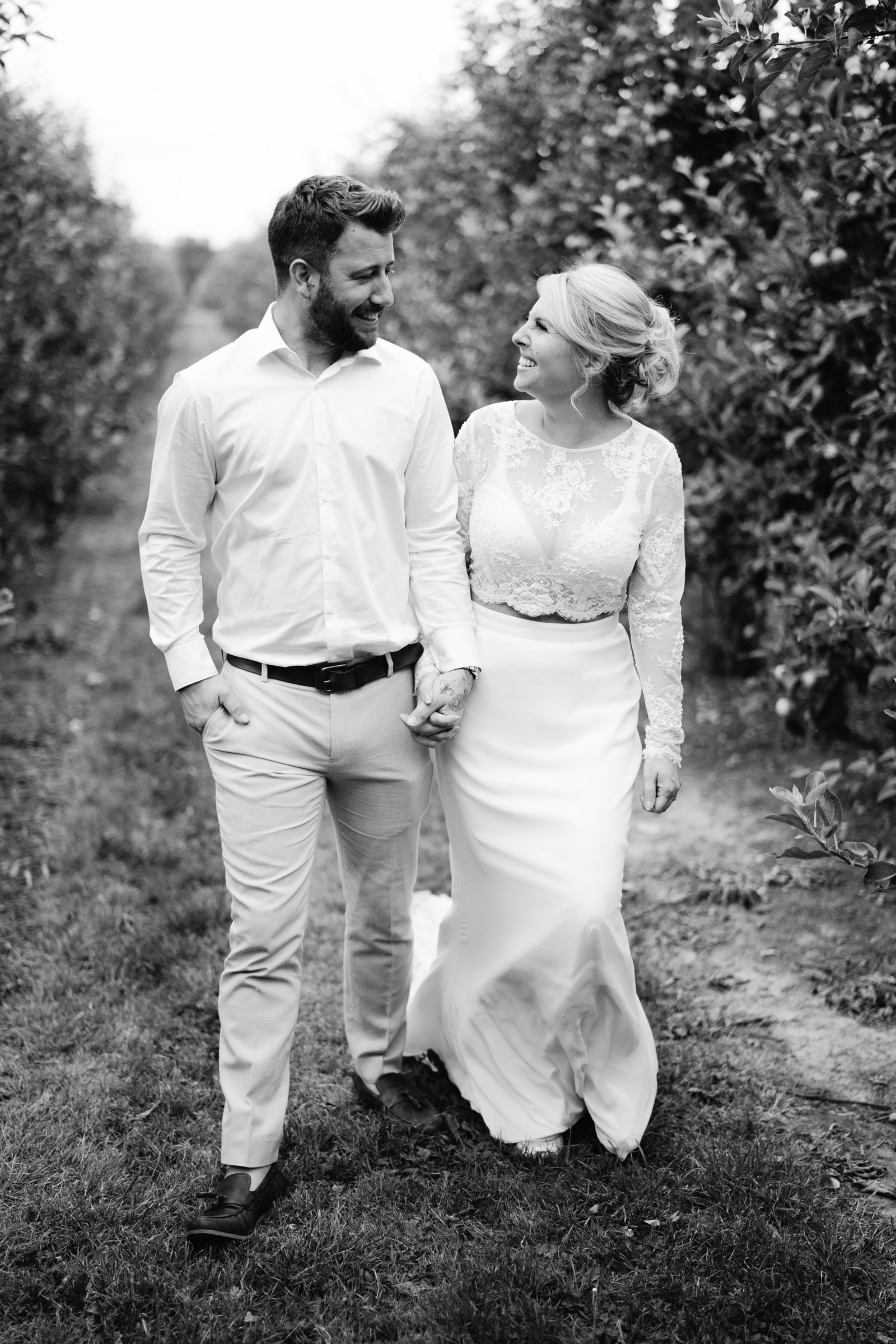 Black and white shot of bride in an orchard, looking lovingly at eachother