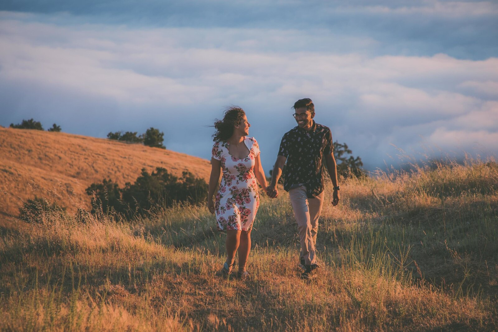 Couple walks at sunset in Big Sur field.