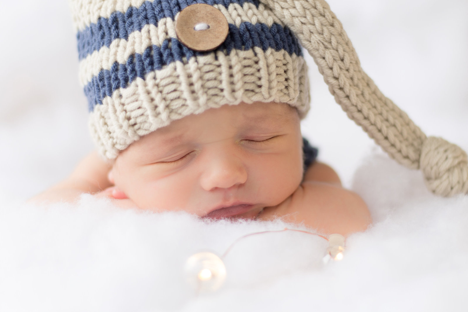 newborn baby boy wearing a striped sleep cap