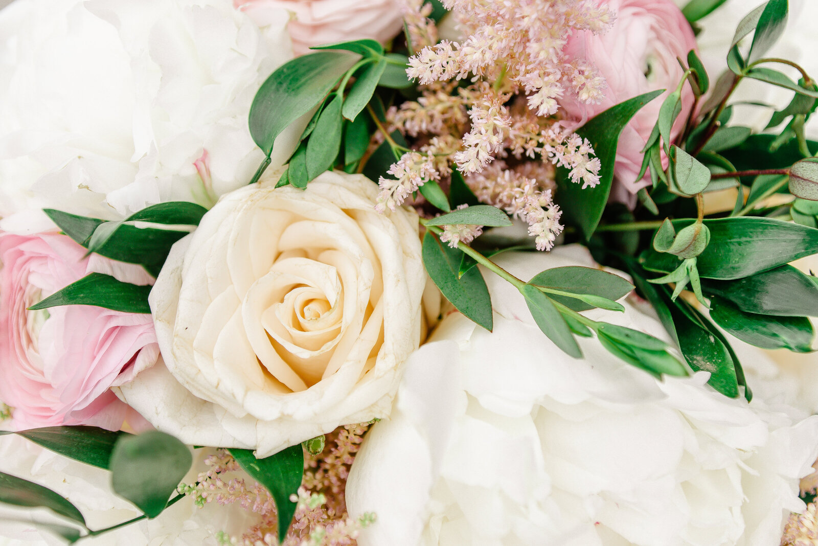 A detail photo of the white and pink blooms in a spring wedding bouquet.