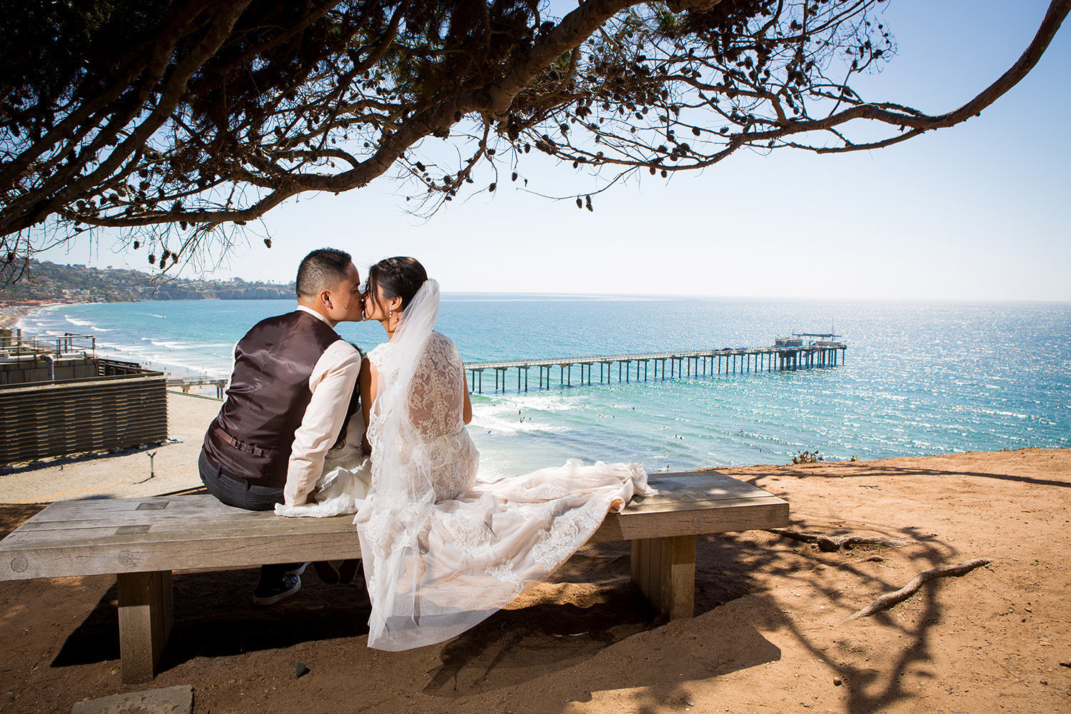 couple kissing at martin johnson house with ocean in background