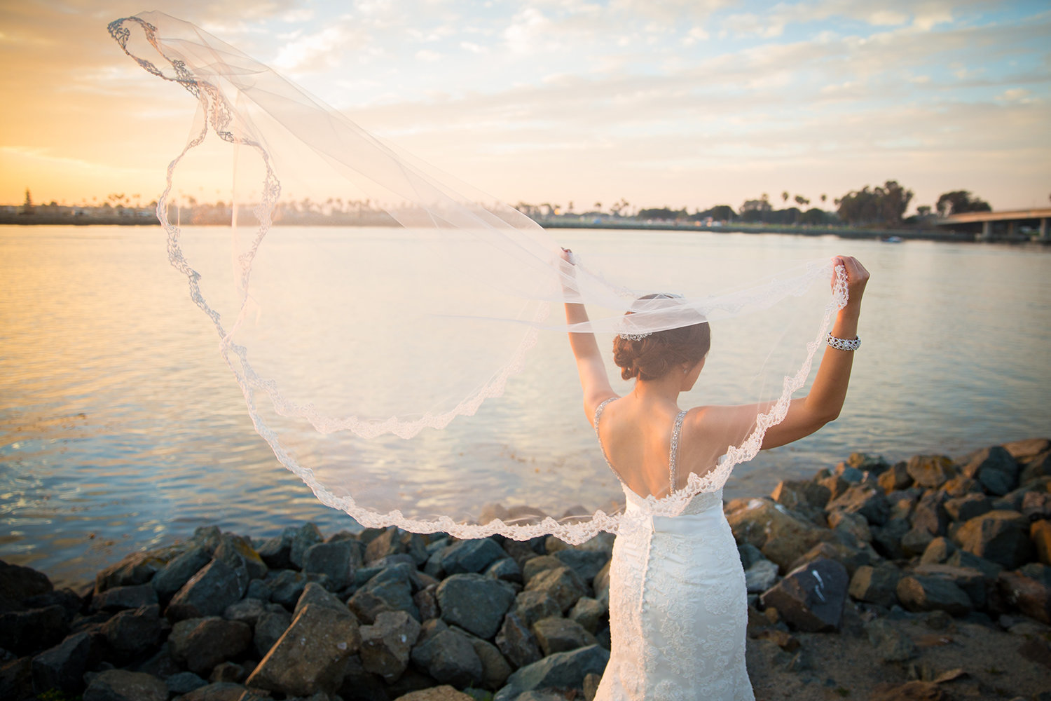 Bride's veil blowing in the wind with a beautiful Misison Bay sunset.