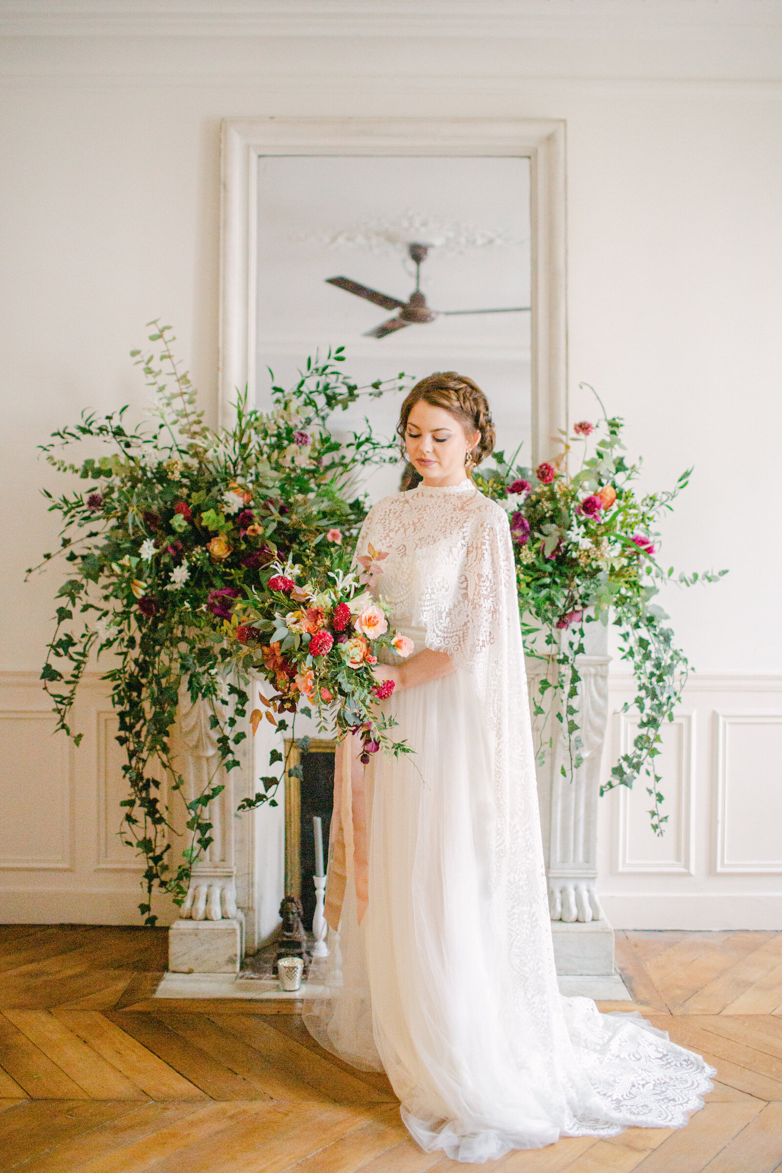 bride holding bouquet and standing in front of fireplace mantel with floral arrangement on it