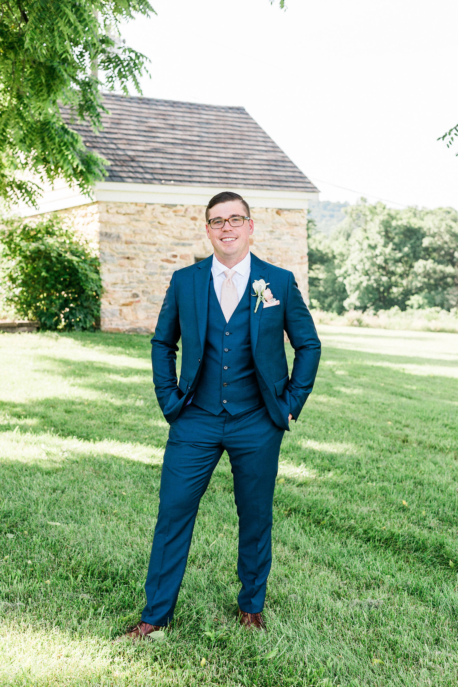 Groom in three piece navy suit poses for a portrait on Springfield Manor Maryland