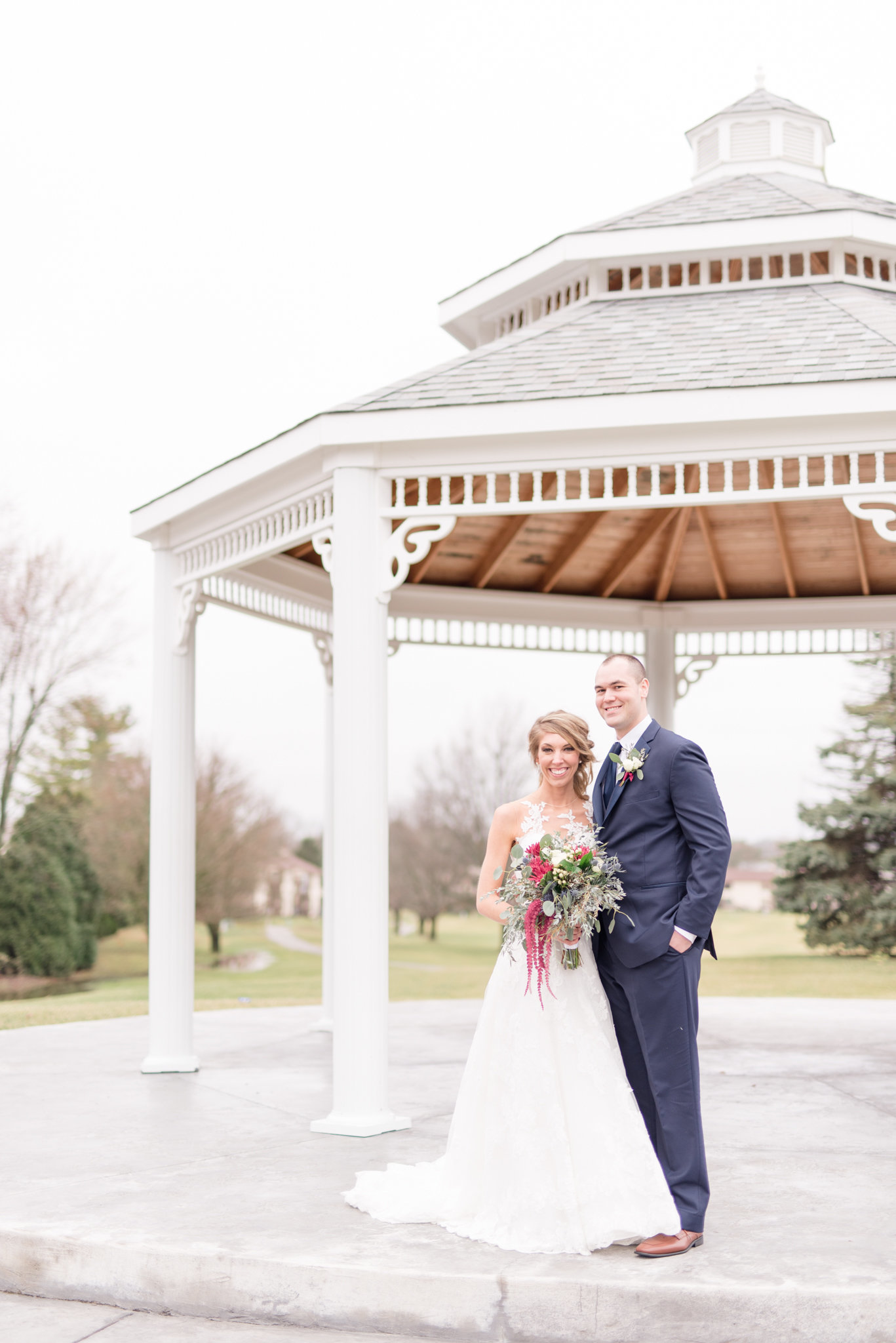 Bride and Groom smile at camera under gazebo.