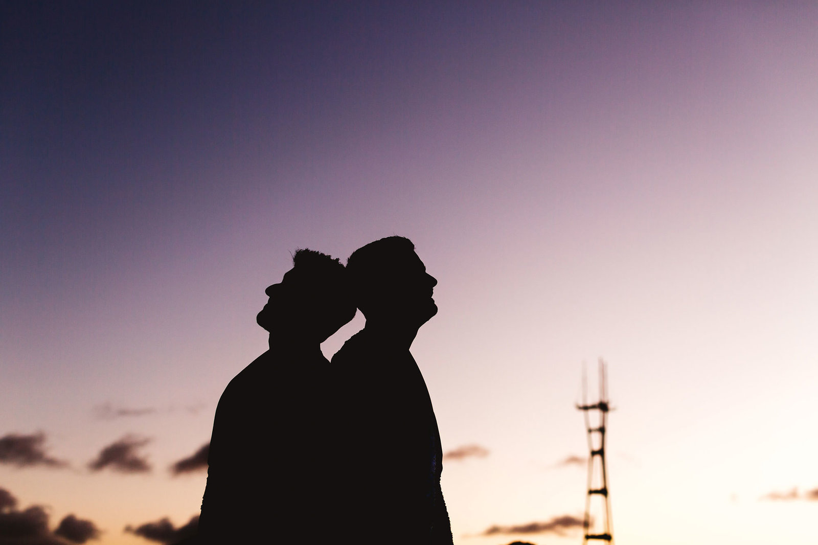 silhouette of two guys in love with sutro tour behind them