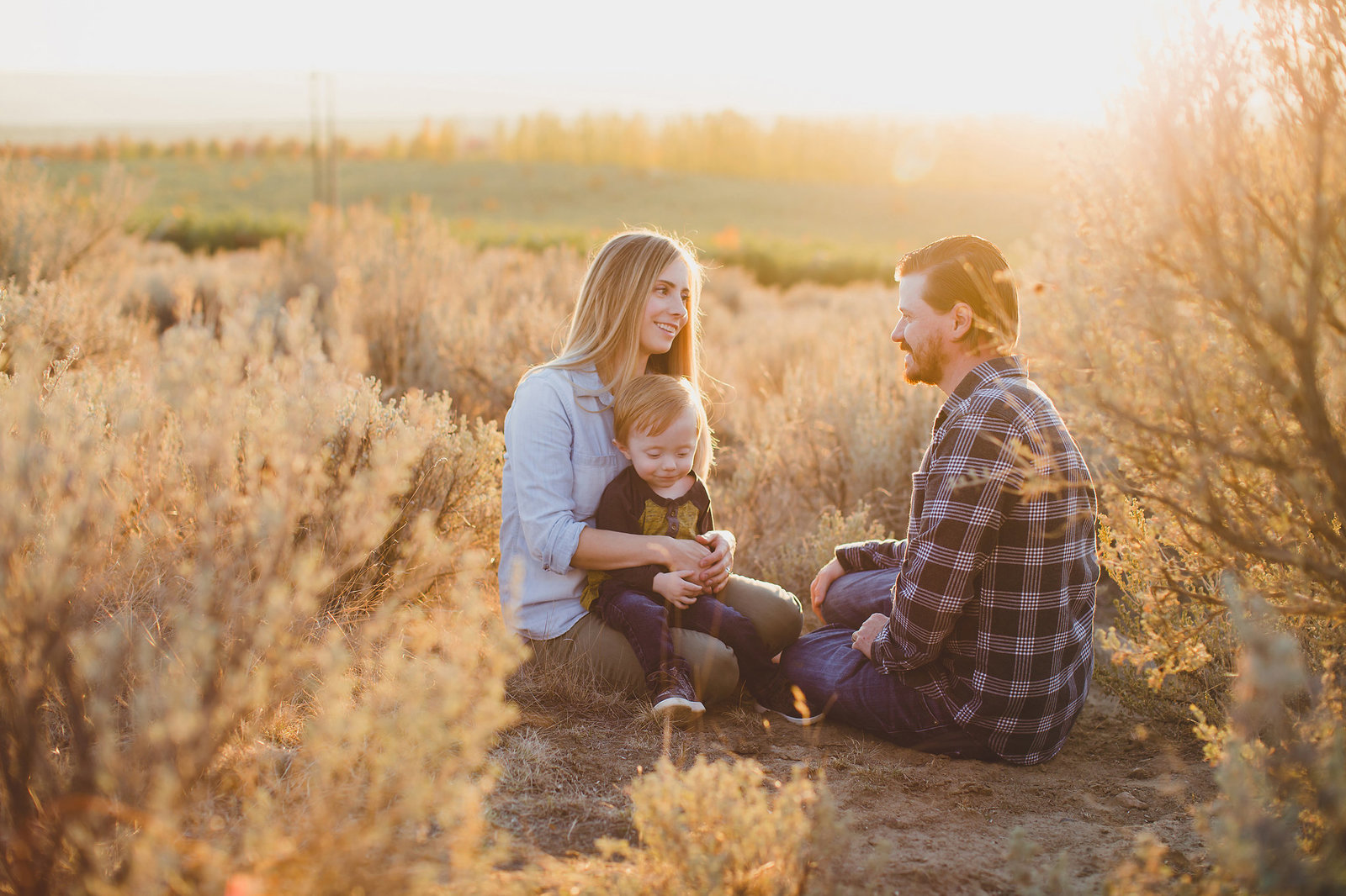 Family of three sitting in the desert sagebrush on Badger Mountain
