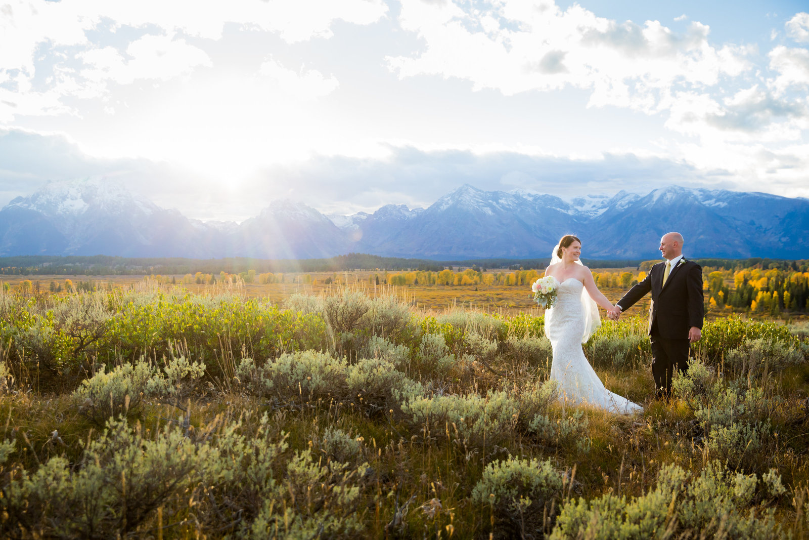 Bride and Groom walking at sunset at Jackson Lake Lodge