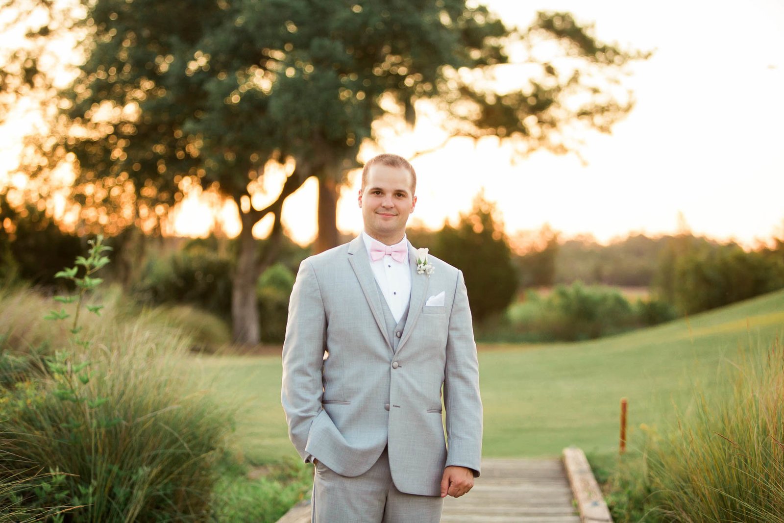 Groom stands in a field at sunset, Daniel Island Club, Charleston Wedding Photography.