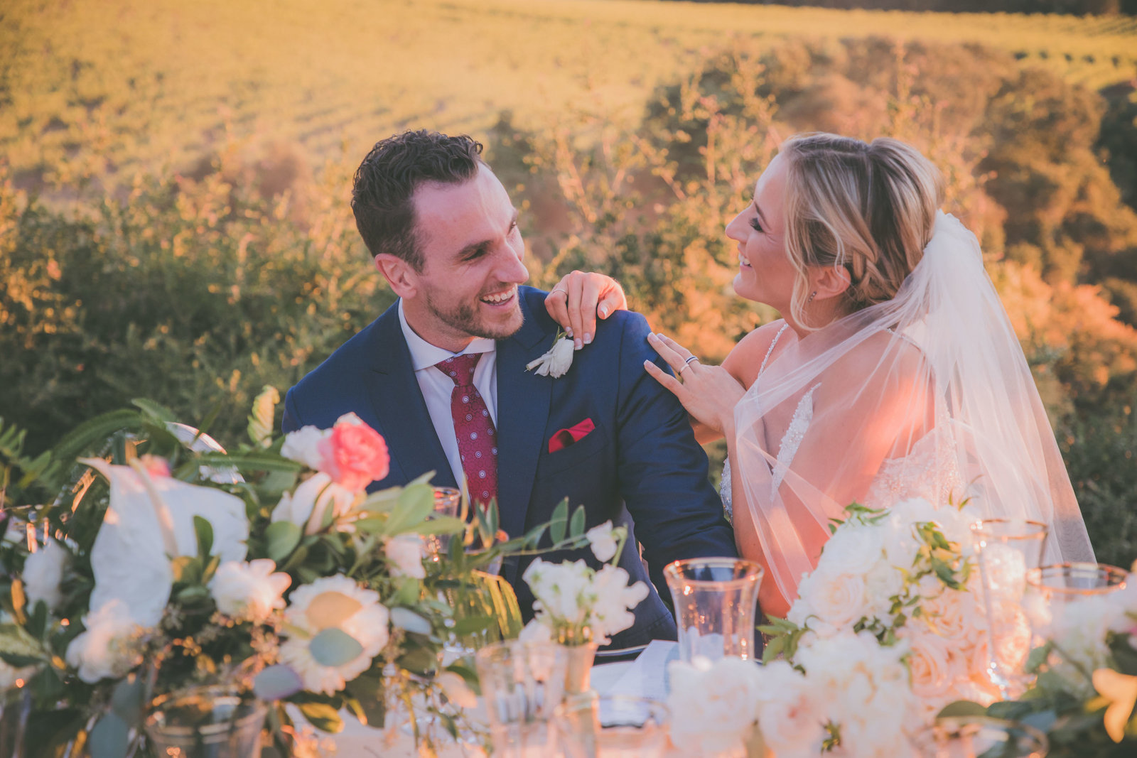Groom laughs at bride during their sunset dinner.