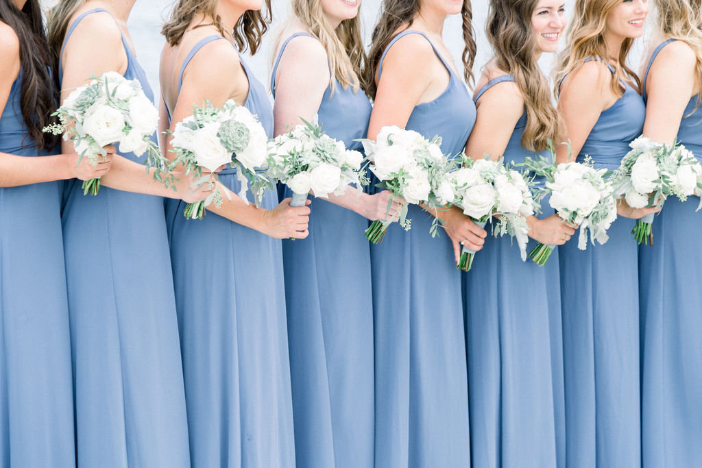 Bride and bridesmaids in grey dresses with eucalyptus bouquets and winter shawls