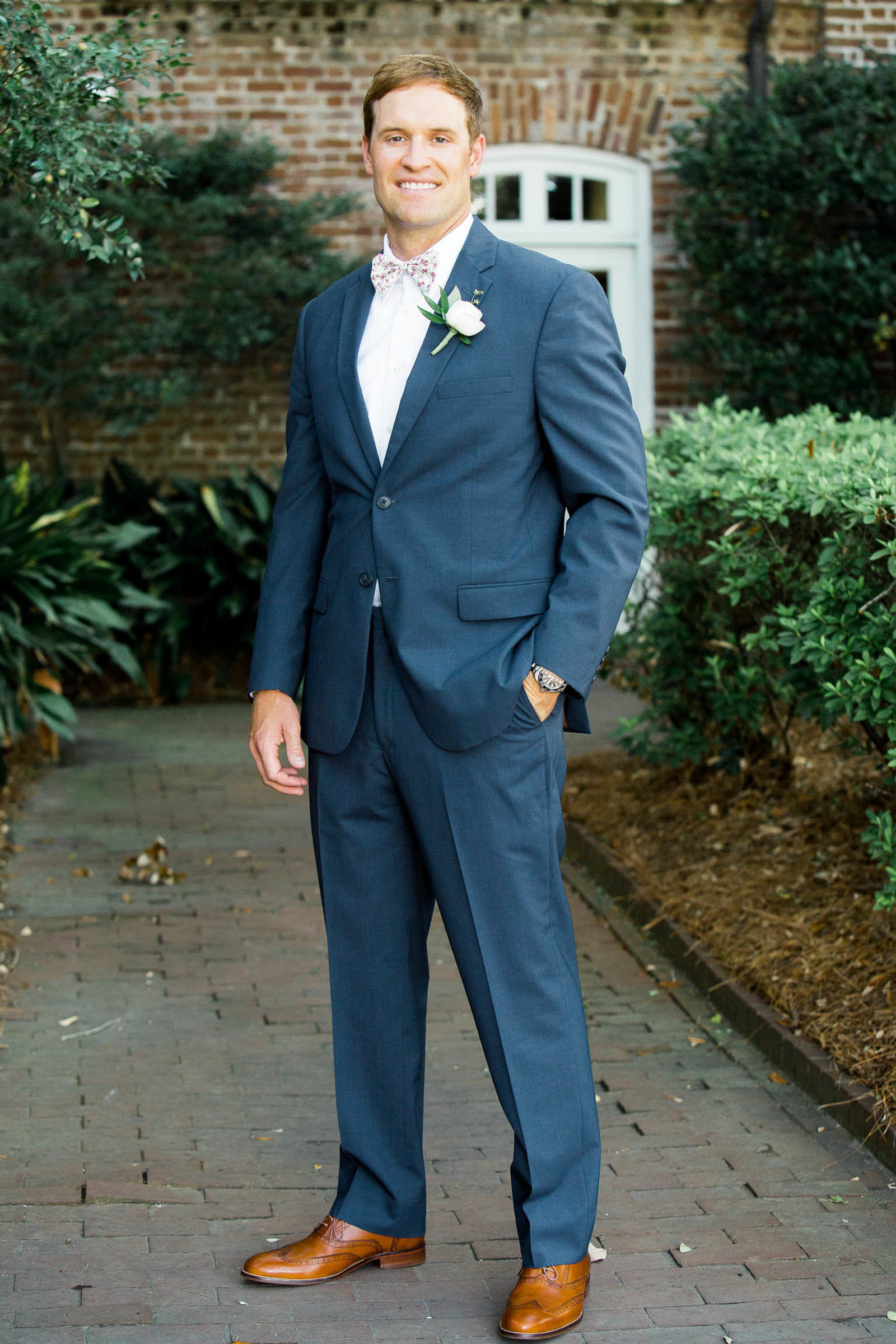 Groom stands in front of the Rice Mill Building, Charleston, South Carolina