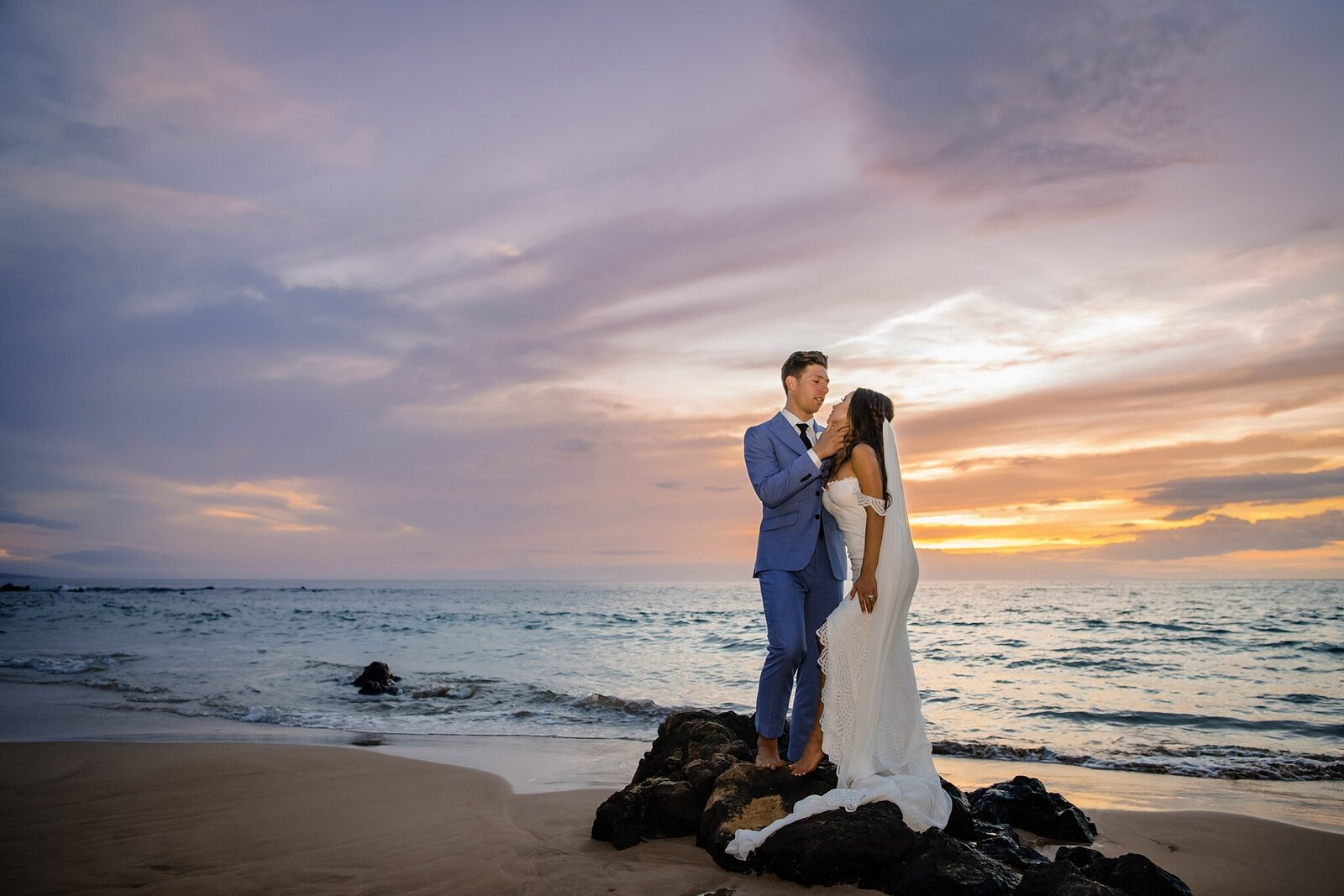 bride and groom against vibrant hawaii sunset