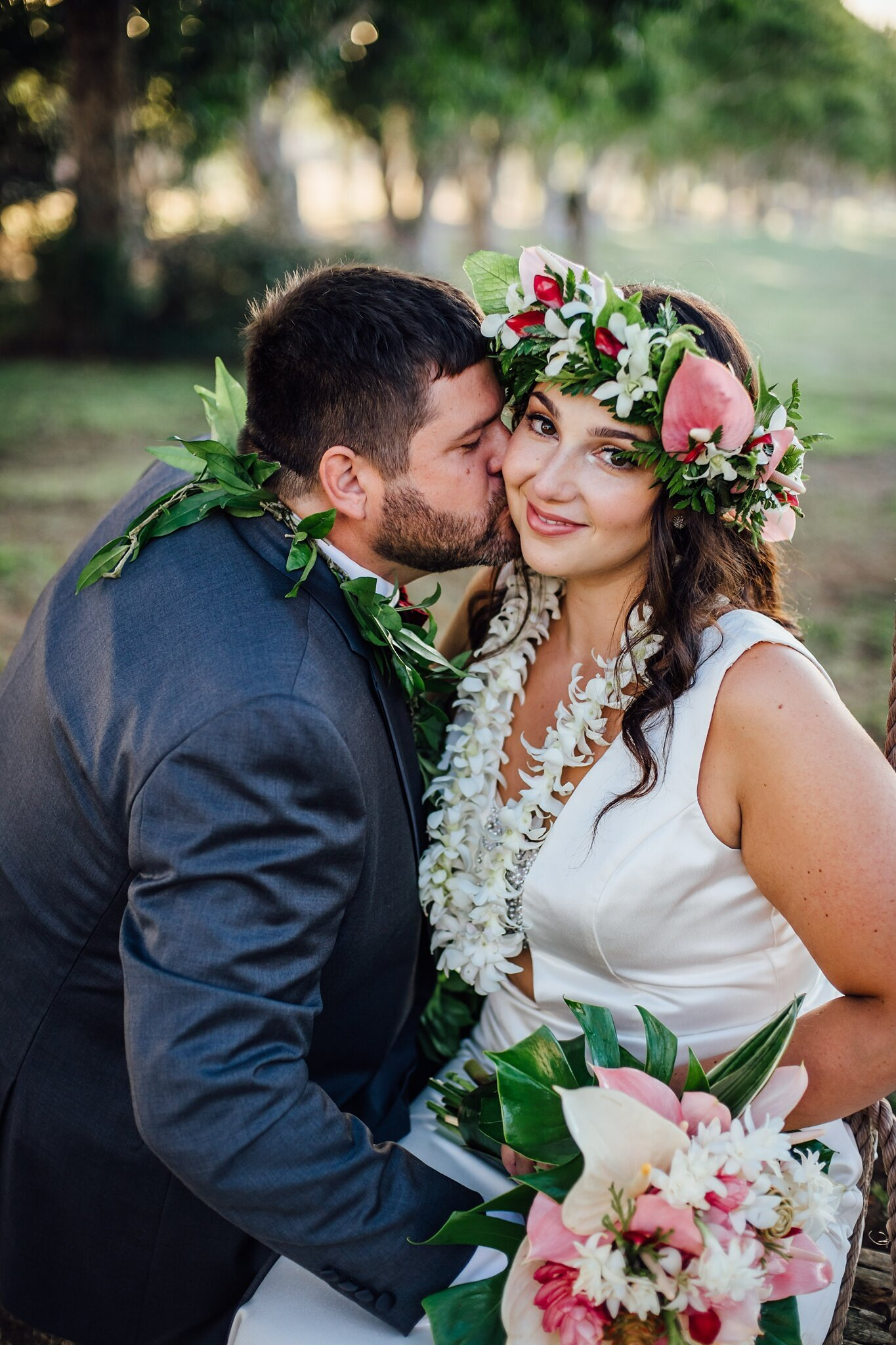 groom kissing bride on cheeks