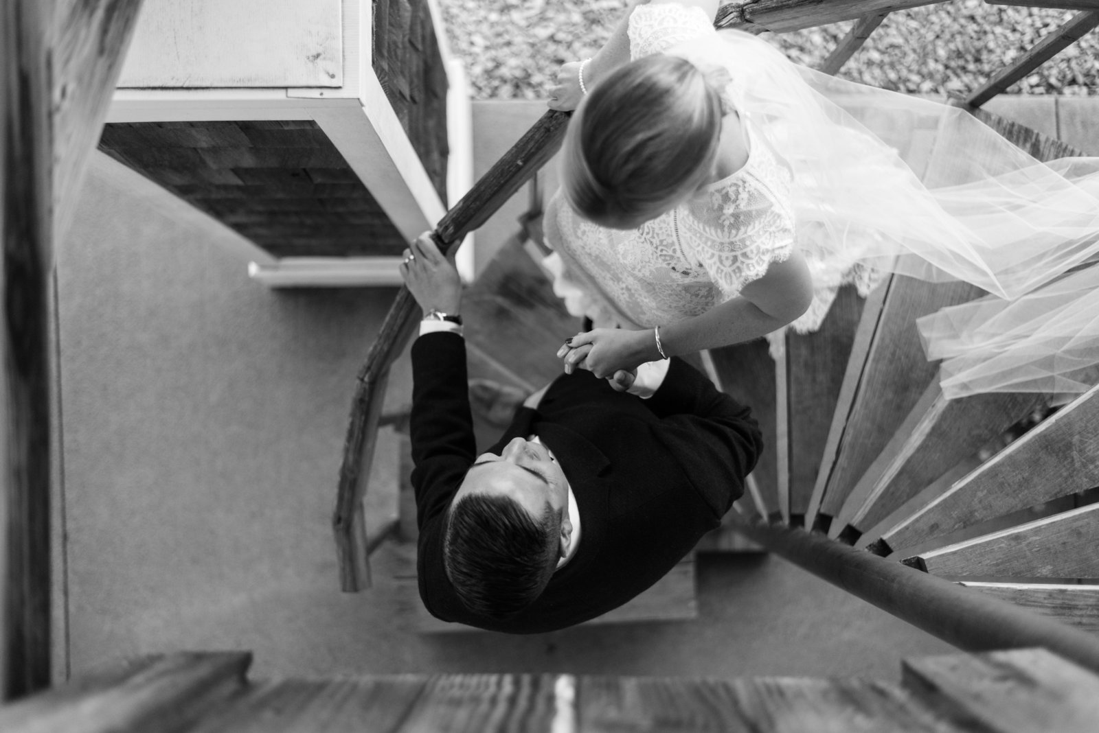 groom leads bride down stairs on wedding day at hermitage hill farm and stables by  waynesboro virginia wedding photographer