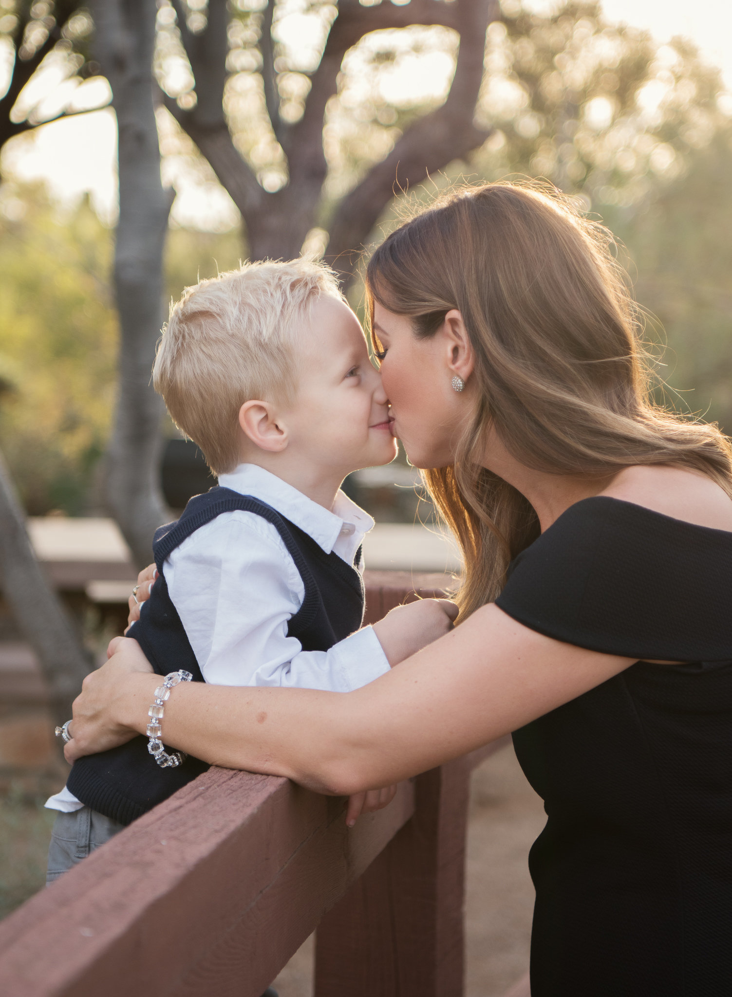 sun shining on mom kissing her son