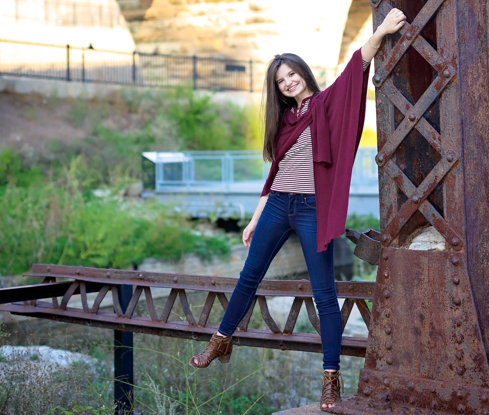 Senior Portrait of girl hanging on to rusty post
