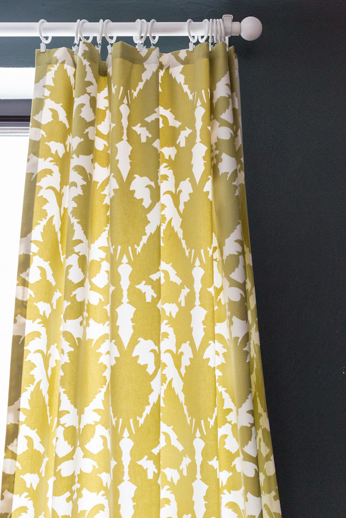 Yellow and white abstract patterned curtains against a dark green wall.