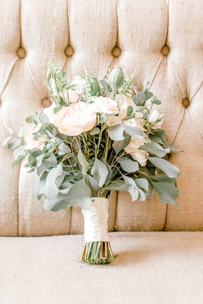 Bridal bouquet with light peach and white flowers with greenery.
