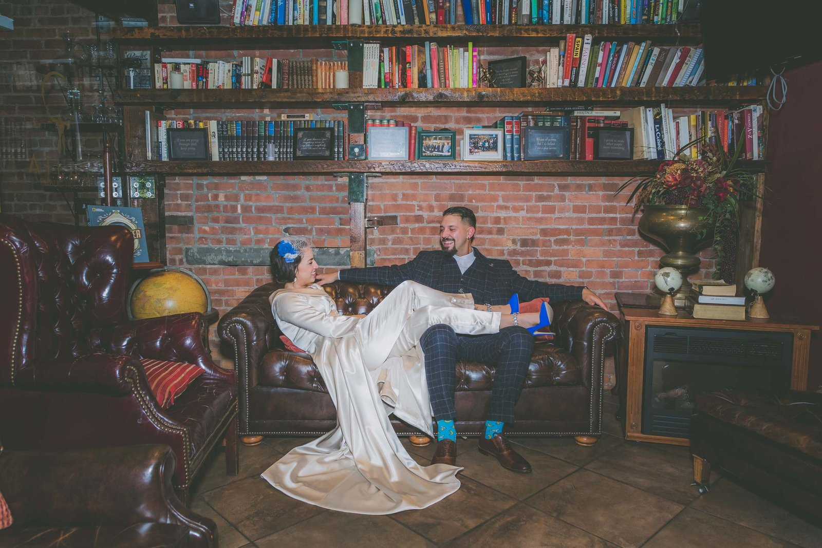 Bride puts feet on top of groom surrounded by books in Jersey City.