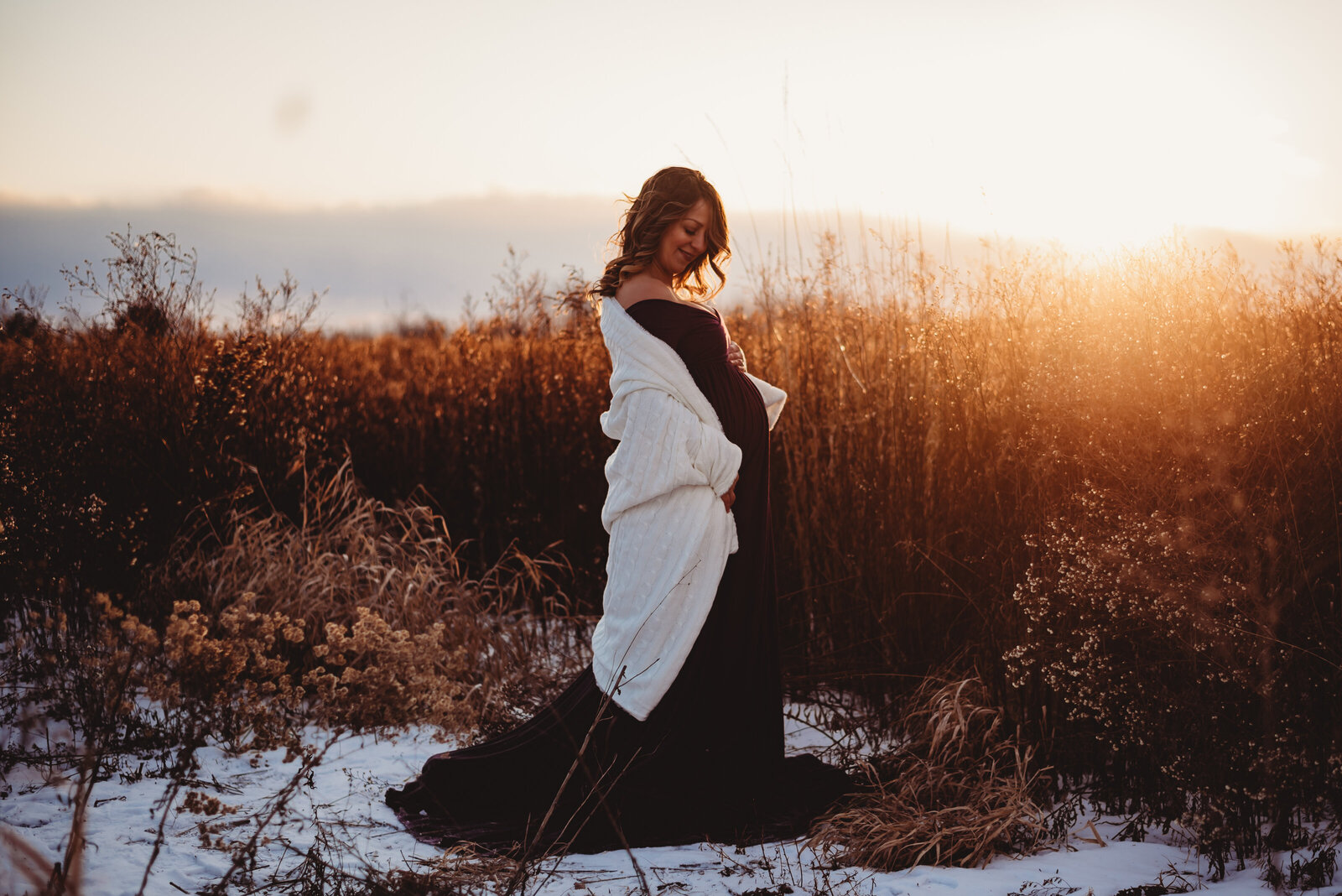Pregnant woman in a field at sunset in Whitby