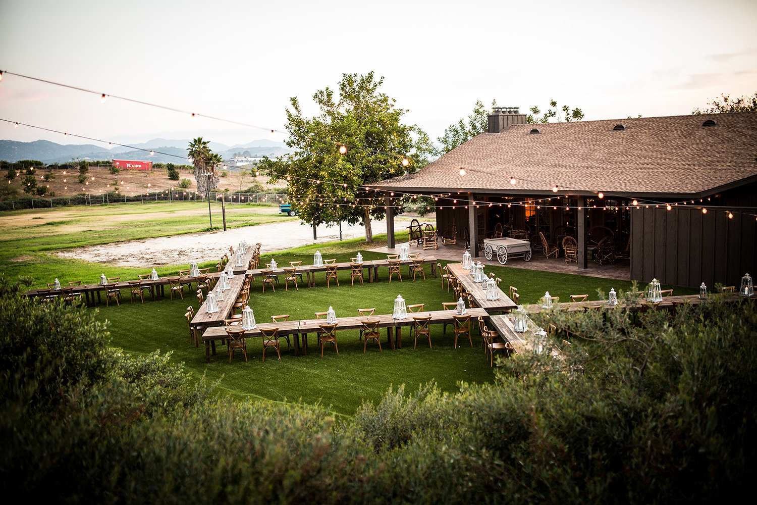 outside reception space with barn tables and rustic barn