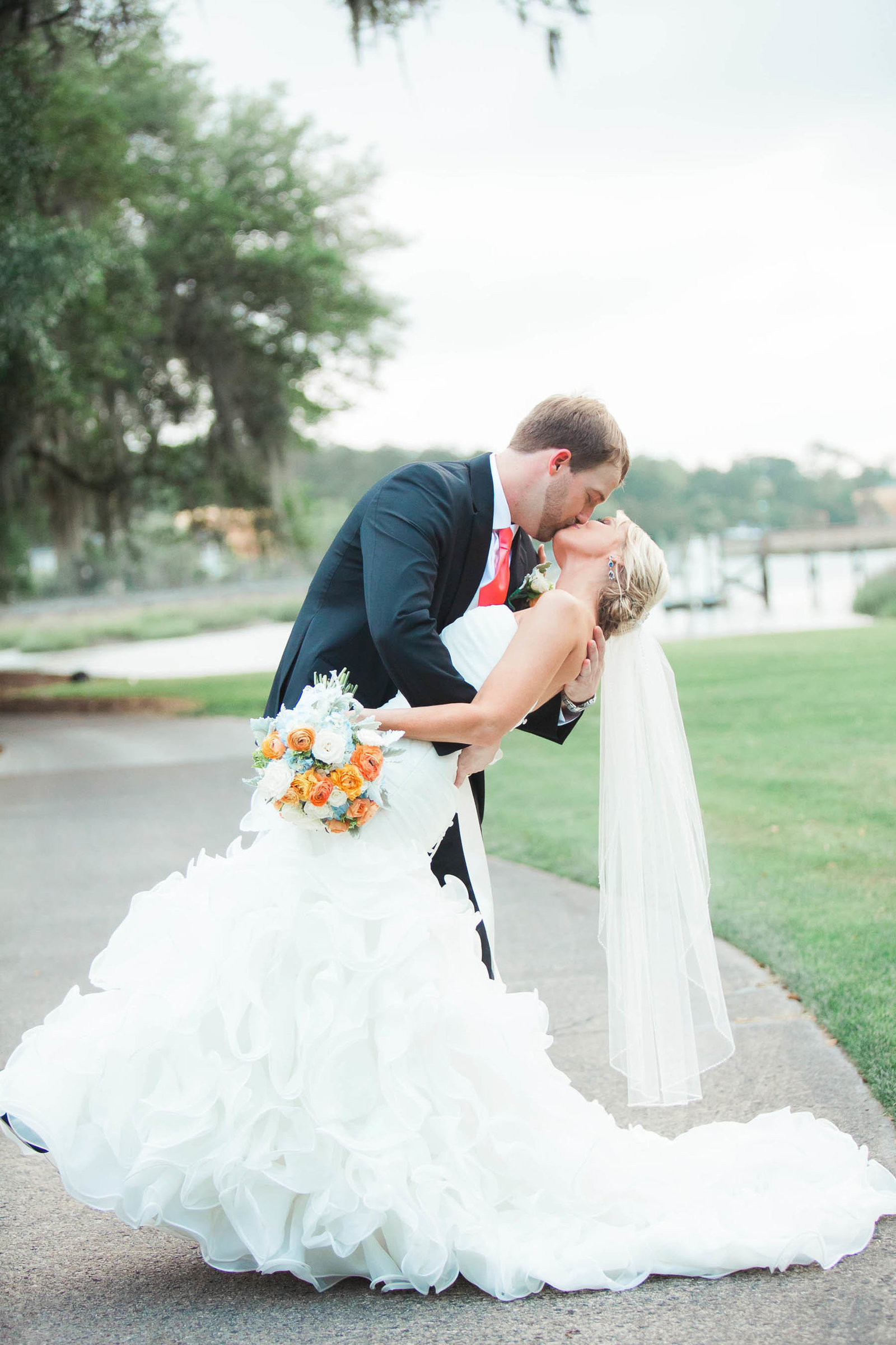 Bride and groom kiss in field, Dunes West Golf and River Club, Mt Pleasant, South Carolina