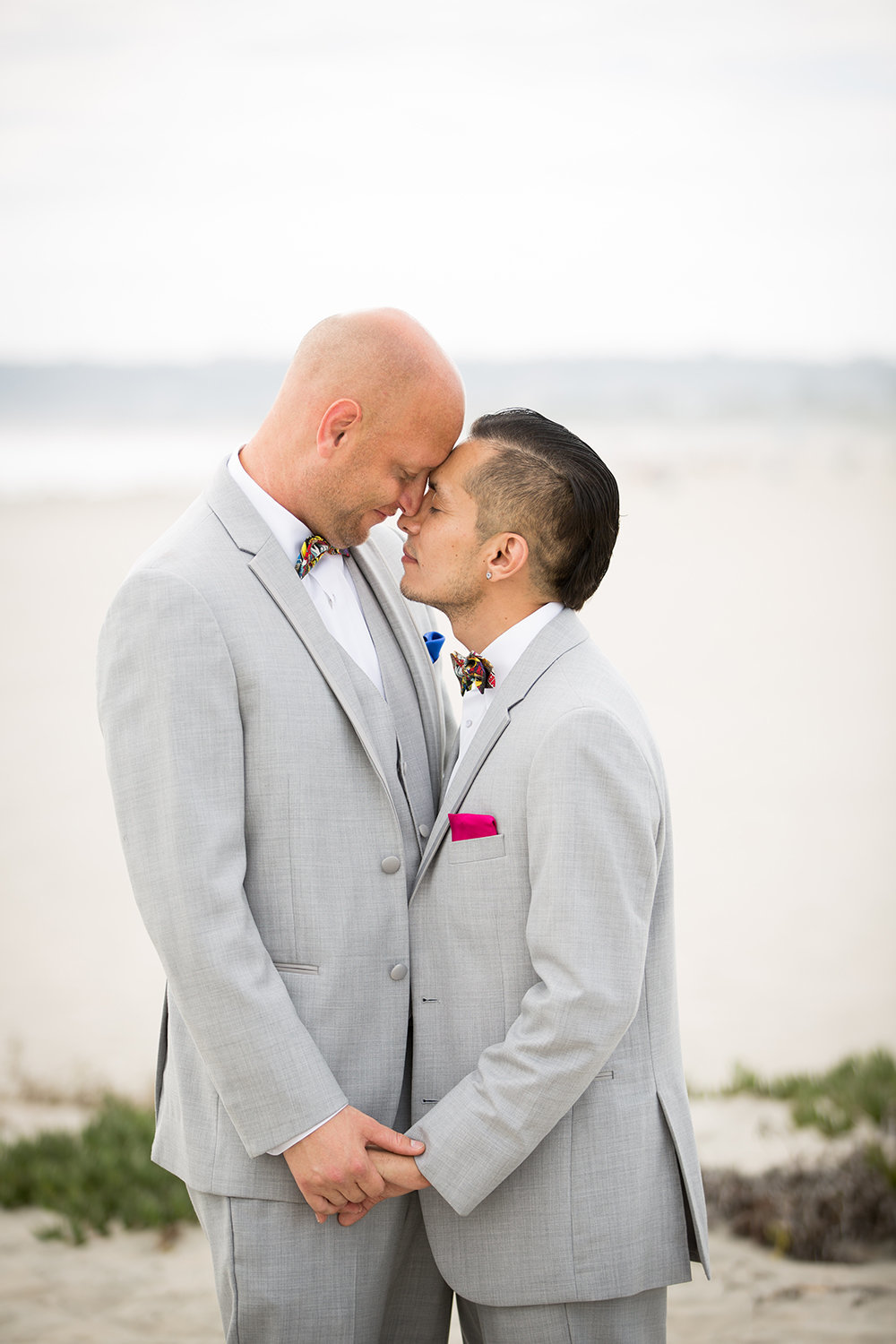 Grooms share a sweet moment at beach in Coronado