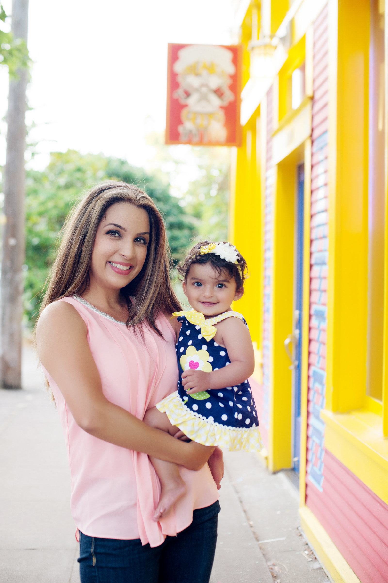 a mom holds her daughter on a very colorful alberta street