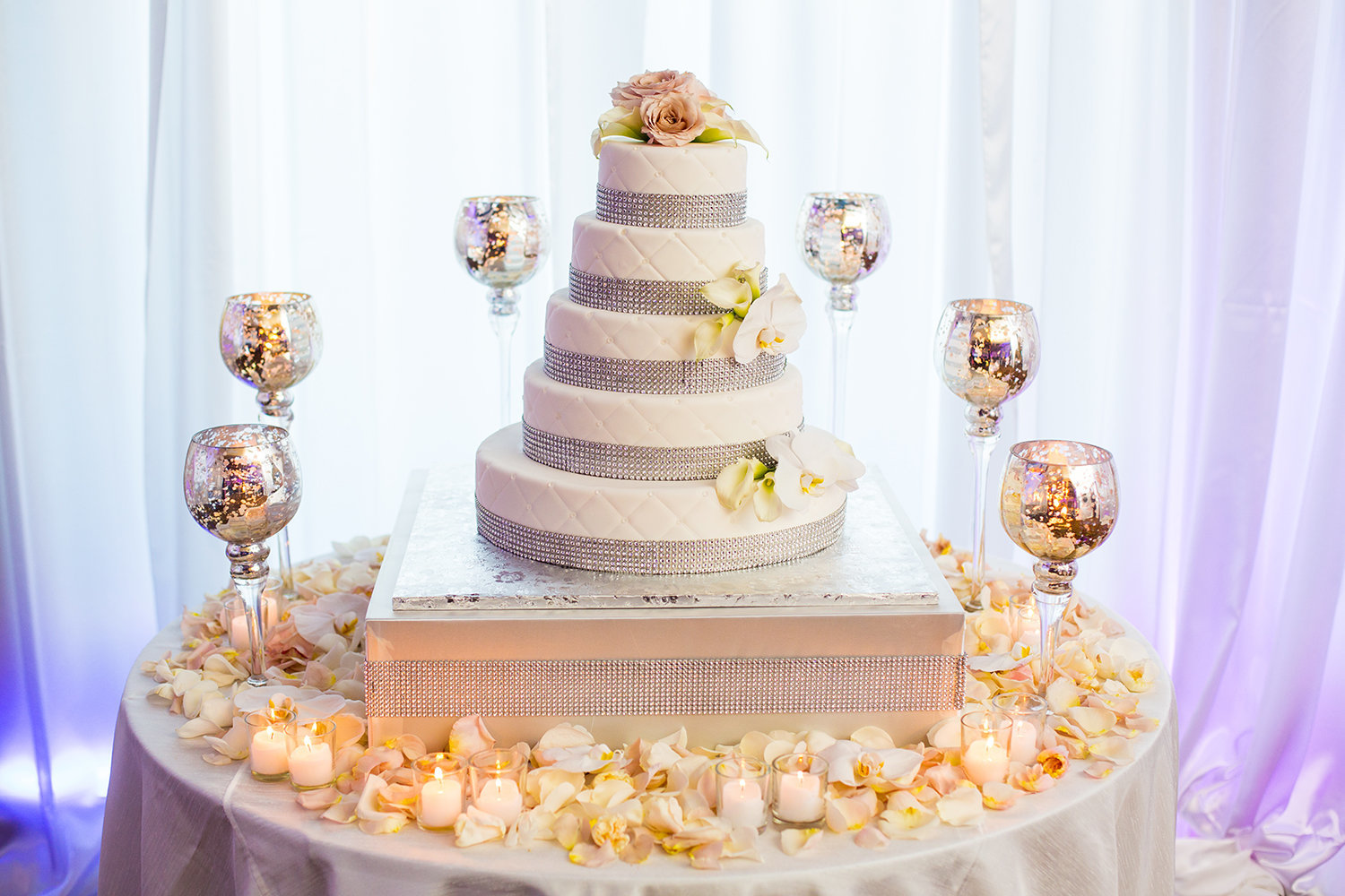 Wedding cake surrounded with candles and adorned with rose petals