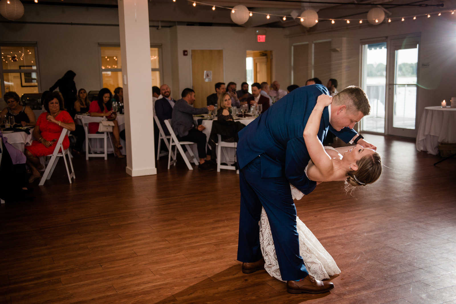 couple shares a dip during their first dance at their duxbury bay maritime school wedding
