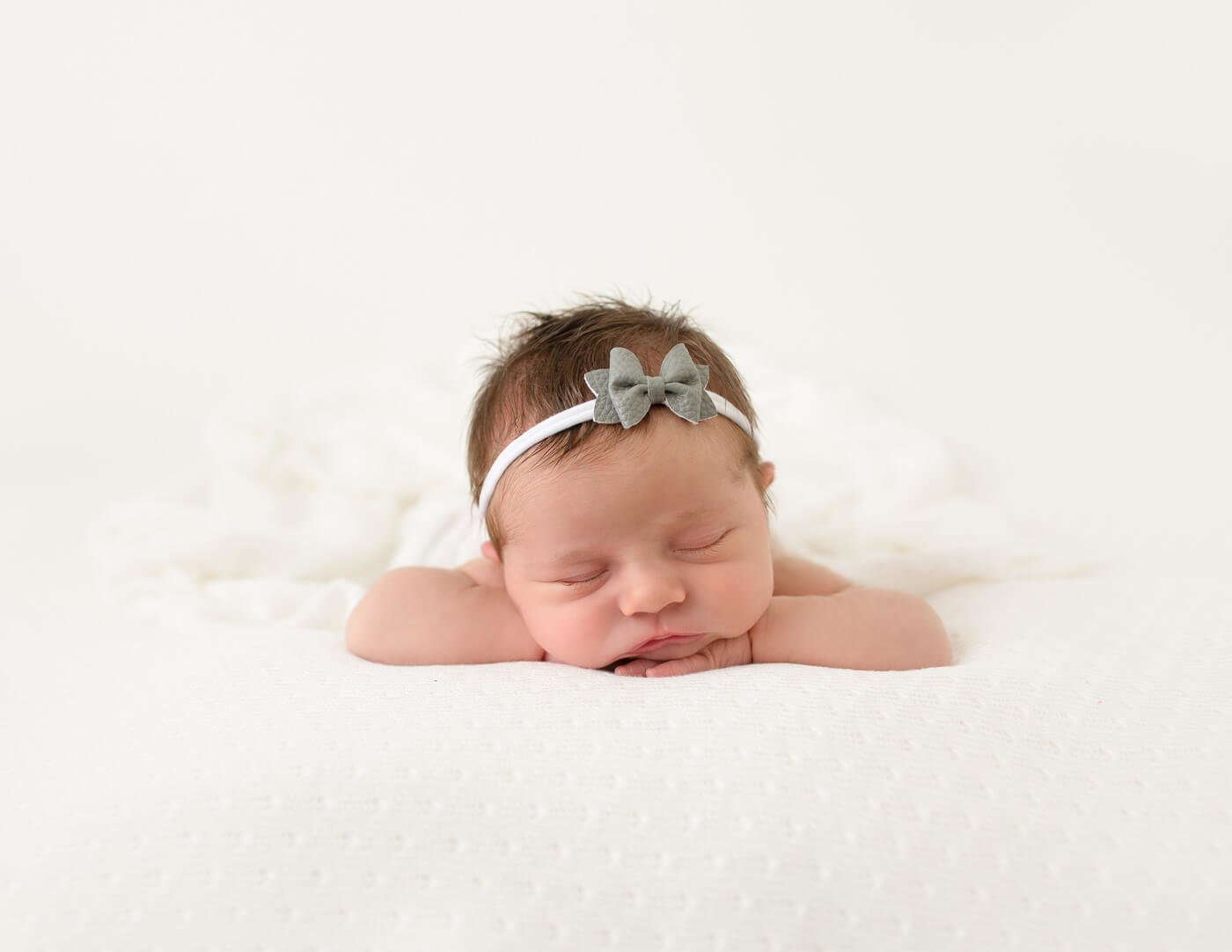 Sweet newborn girl in head on hands pose in studio.
