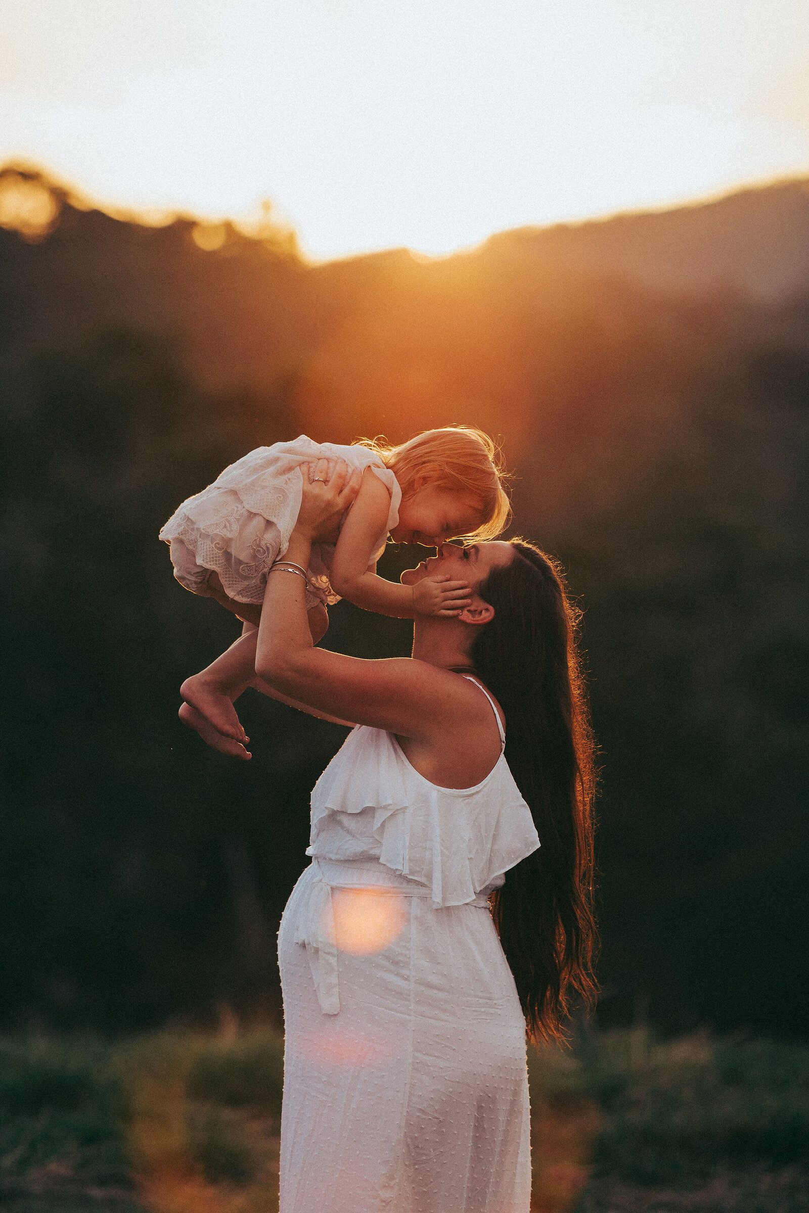 Professional maternity portrait outdoors, mother holding daughter in air