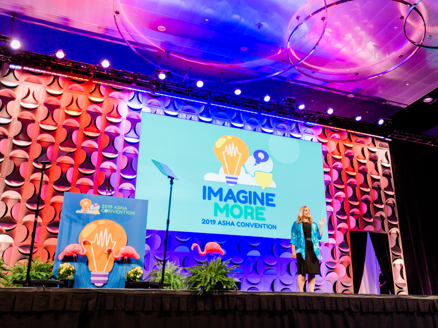 Woman on a colorful stage at a conference giving a speech