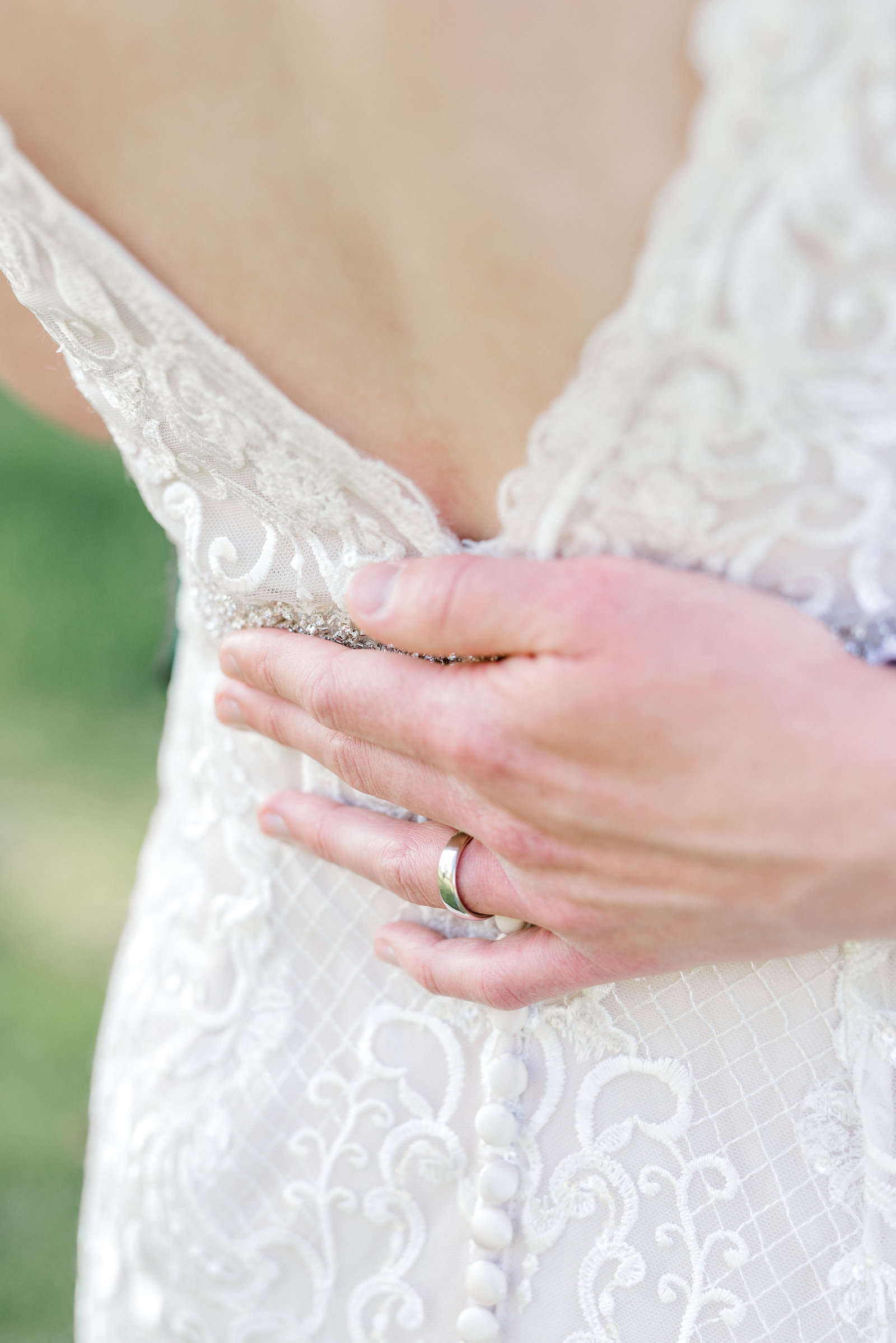 Grooms Hand on back of ornate bridal gown