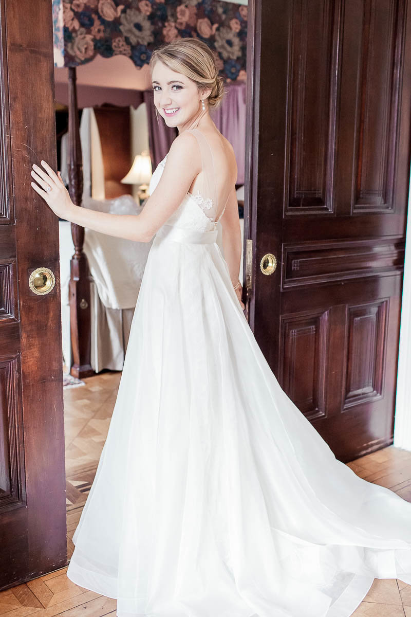 Bride stands by wooden sliding doors, John Rutledge House Inn, Charleston, South Carolina